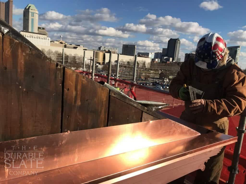 durable slate employee measuring a piece of copper