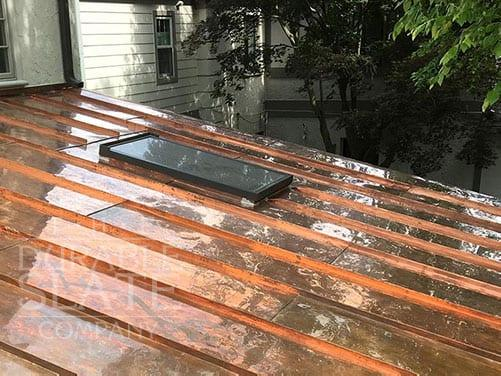 a new standing seam copper roof with a skylight and trees in the background