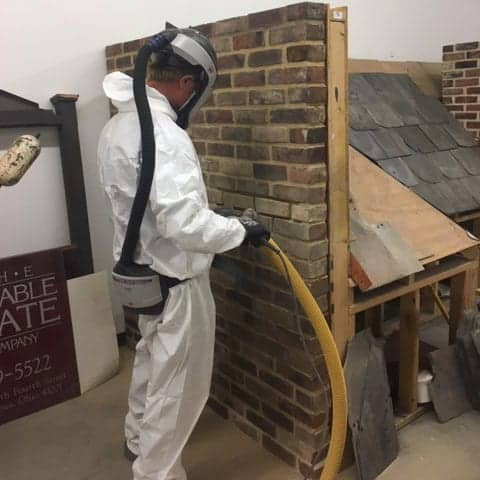 durable slate employee learning the correct way to saw through antique masonry in a full hazmat suit
