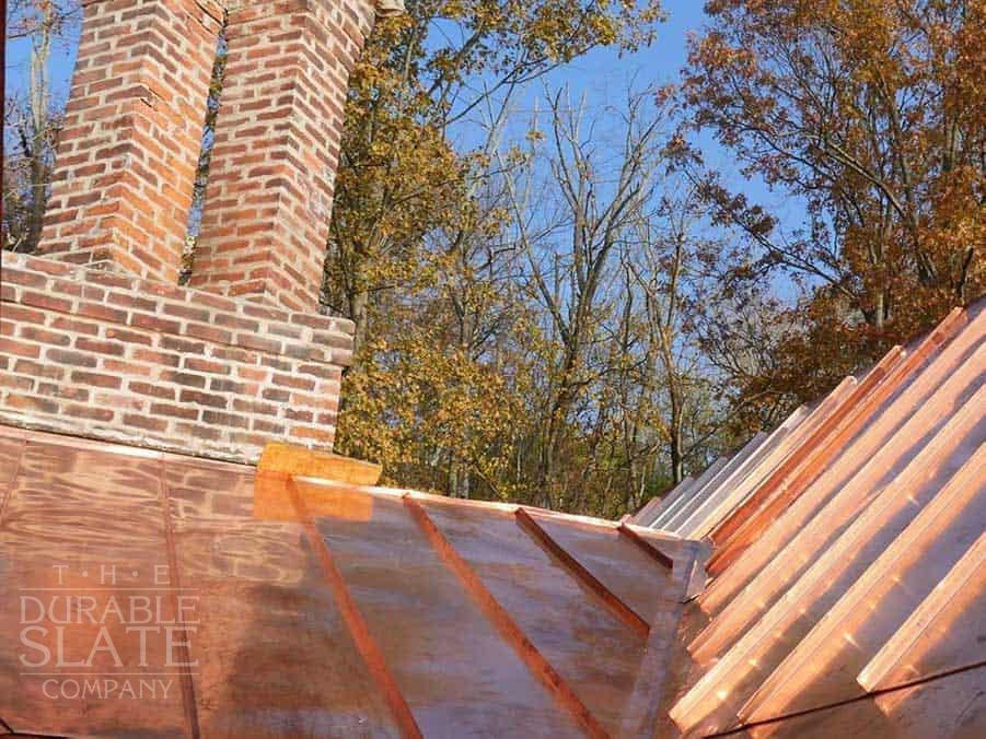 cincinnati copper standing seam roof with fall foliage and chimney in the background