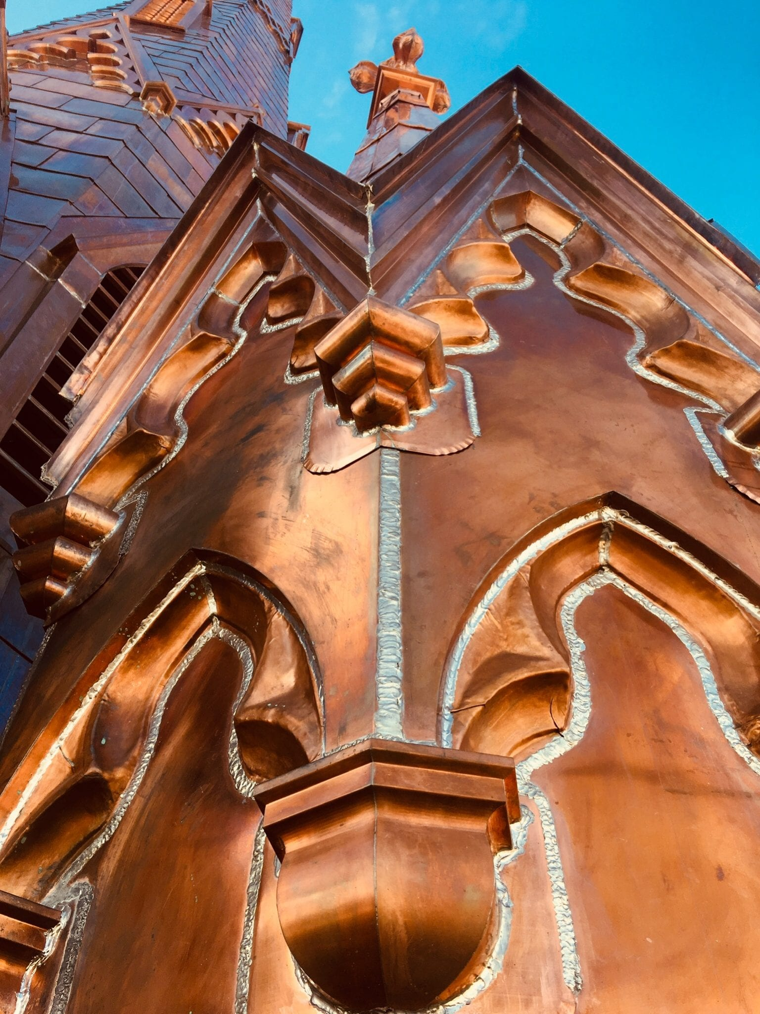 close up of steeple square copper welding work with blue sky in the background