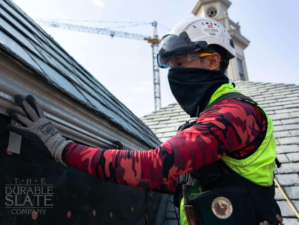 the durable slate company employee inspecting a slate roof under repair in city ridge washington d.c.